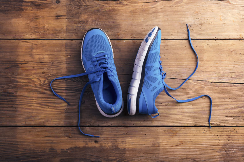 38905988 - pair of blue running shoes laid on a wooden floor background