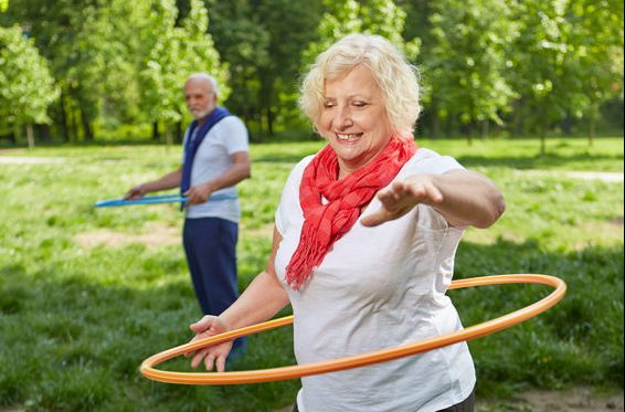 47618043 - two happy senior people using hoops in a park for a fitness training